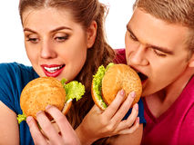 Woman feeds man fast food together. Stock Photos