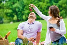 Woman feeds man in park Stock Images