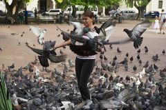 Woman feeds pigeons in Santo Domingo, Dominican Republic. Royalty Free Stock Image