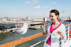 Woman feeds seagull on deck of ship. Stock Photo