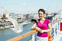 Woman feeds seagulls on deck of ship Stock Images