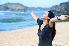 Woman feel free and relax. At beach express when she raised her hand to the top Stock Photos