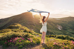Woman feel freedom and enjoying the nature. In the mountains with blue tissue in hands on sunset Stock Photo