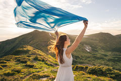 Woman feel freedom and enjoying the nature. In the mountains with blue tissue in hands on sunset Royalty Free Stock Images