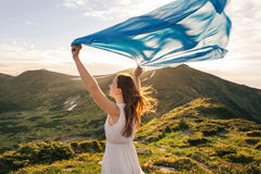 Woman feel freedom and enjoying the nature. In the mountains with blue tissue in hands on sunset stock photography
