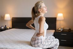 Woman feeling back pain after sleeping in bed at home stock image