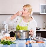 Woman feeling bad smell from pan. Unhappy young housewife preparing exotic food with rank odour at kitchen stock photos