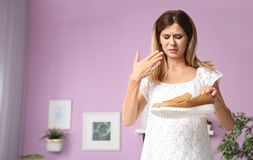Woman feeling bad smell from shoes at home royalty free stock photography