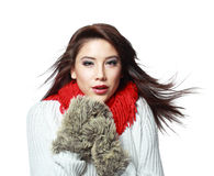 Woman feeling cold. Beautiful young woman feeling cold wind in winter hearing warm closthes and fur gloves isolated over white Stock Image