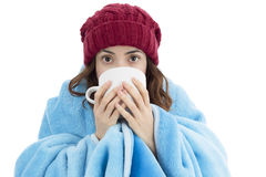 Woman feeling cold and drinking warm tea. Woman feeling cold, covered with blanket and drinking some hot beverage. Isolated on white background Stock Photography