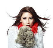 Woman feeling cold wind. Beautiful young woman feeling cold wind in winter hearing warm closthes and fur gloves isolated over white Stock Image