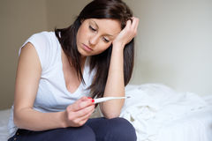 Woman feeling depressed and sad after looking at pregnancy test. Result Royalty Free Stock Photography