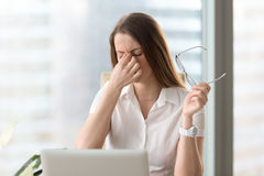 Woman feeling discomfort from long wearing glasses. Tired businesswoman holding eyeglasses and massaging nose bridge. Girl feeling discomfort from long wearing Royalty Free Stock Photography
