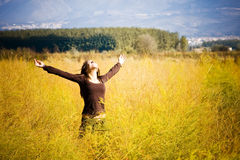 Woman feeling freedom in a field. Stock Images