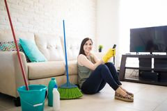 Adorable woman sitting on clean floor using smartphone. Woman feeling good after completing house chores using smartphone and looking at camera Royalty Free Stock Image