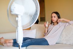 Woman feeling hot and trying to refresh in summertime heat. Young woman relaxing under the air fan at home Royalty Free Stock Images
