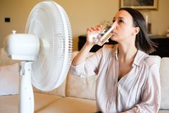 Young woman relaxing under the air fan at home. Woman feeling hot and trying to refresh in summertime heat Royalty Free Stock Image