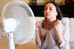 Woman feeling hot and trying to refresh in summertime heat. Young woman relaxing under the air fan at home Royalty Free Stock Photos