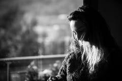 Woman feeling nostalgic at the window Stock Image