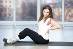 Woman feeling pain in back during sport exercise Stock Photos