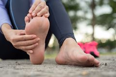 Pain foot during sport. Woman feeling pain in her foot during sport outdoor royalty free stock image