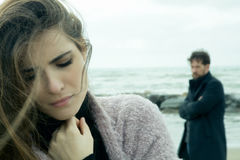Woman feeling sad about relationship. Unhappy couple after fight feeling sad in front of the ocean Royalty Free Stock Photos