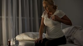 Woman feeling sharp pain in her chest, suffering heart attack at night, health. Stock photo stock images