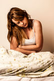 Woman feeling sick with stomachache in bed - Pain in stomach Stock Photography