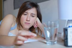 Woman ready to eat medicine pill lying in bed stock photography
