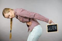 Woman feeling stomach cramps holding gluten board Stock Photos