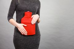 Woman feeling stomach cramps holding hot water bottle Royalty Free Stock Photo