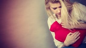 Woman feeling stomach cramps holding hot water bottle Stock Image