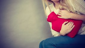 Woman feeling stomach cramps holding hot water bottle Royalty Free Stock Photos