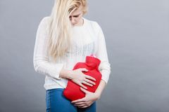 Woman feeling stomach cramps holding hot water bottle. Painful periods and menstrual cramp problems concept. Woman having stomach cramps feeling very unwell Stock Image