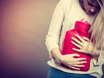 Woman feeling stomach cramps holding hot water bottle. Painful periods and menstrual cramp problems concept. Woman having stomach cramps feeling very unwell Royalty Free Stock Photo