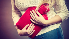 Woman feeling stomach cramps holding hot water bottle Stock Photo