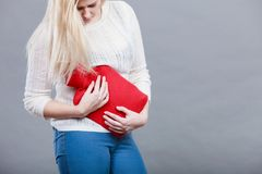 Woman feeling stomach cramps holding hot water bottle Stock Photography