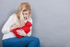 Woman feeling stomach cramps holding hot water bottle. Painful periods and menstrual cramp problems concept. Woman having stomach cramps feeling very unwell Royalty Free Stock Images
