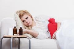 Woman feeling stomach cramps lying on cofa Royalty Free Stock Photography