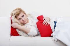 Woman feeling stomach cramps lying on cofa Stock Image