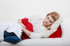 Woman feeling stomach cramps lying on cofa Stock Photo
