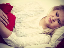 Woman feeling stomach cramps lying on cofa Royalty Free Stock Photos