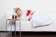 Woman feeling stomach cramps lying on cofa Stock Images