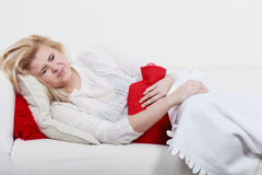 Woman feeling stomach cramps lying on cofa Stock Photo