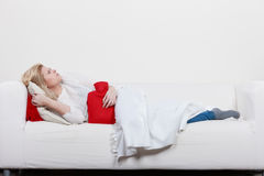 Woman feeling stomach cramps lying on cofa Royalty Free Stock Photography