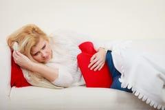 Woman feeling stomach cramps lying on cofa Stock Photos