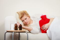 Woman feeling stomach cramps lying on cofa Royalty Free Stock Photo