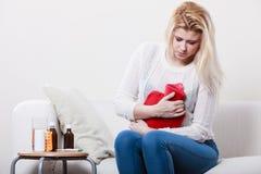 Woman feeling stomach cramps sitting on cofa Stock Photos