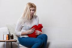 Woman feeling stomach cramps sitting on cofa Royalty Free Stock Images