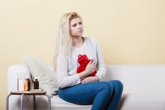 Woman feeling stomach cramps sitting on cofa. Painful periods and menstrual cramp problems concept. Woman having stomach cramps sitting on cofa feeling very Royalty Free Stock Photos
